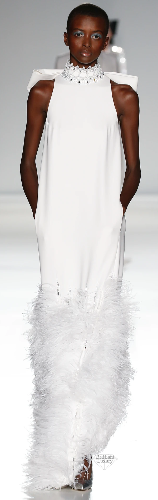 white silk crêpe halterneck column gown embellished with xilions crystals pearlescent sequins and ostrich feathers and finished with an oversized bow #brilliantluxury
